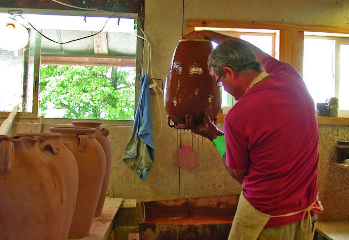 Ellington glazing a jar in the alkaline glaze he learned from Burlon Craig. The glaze consists of wood ash, crushed glass, and clay slip. Vale, North Carolina, 2013. Photograph courtesy of Kim Ellington.