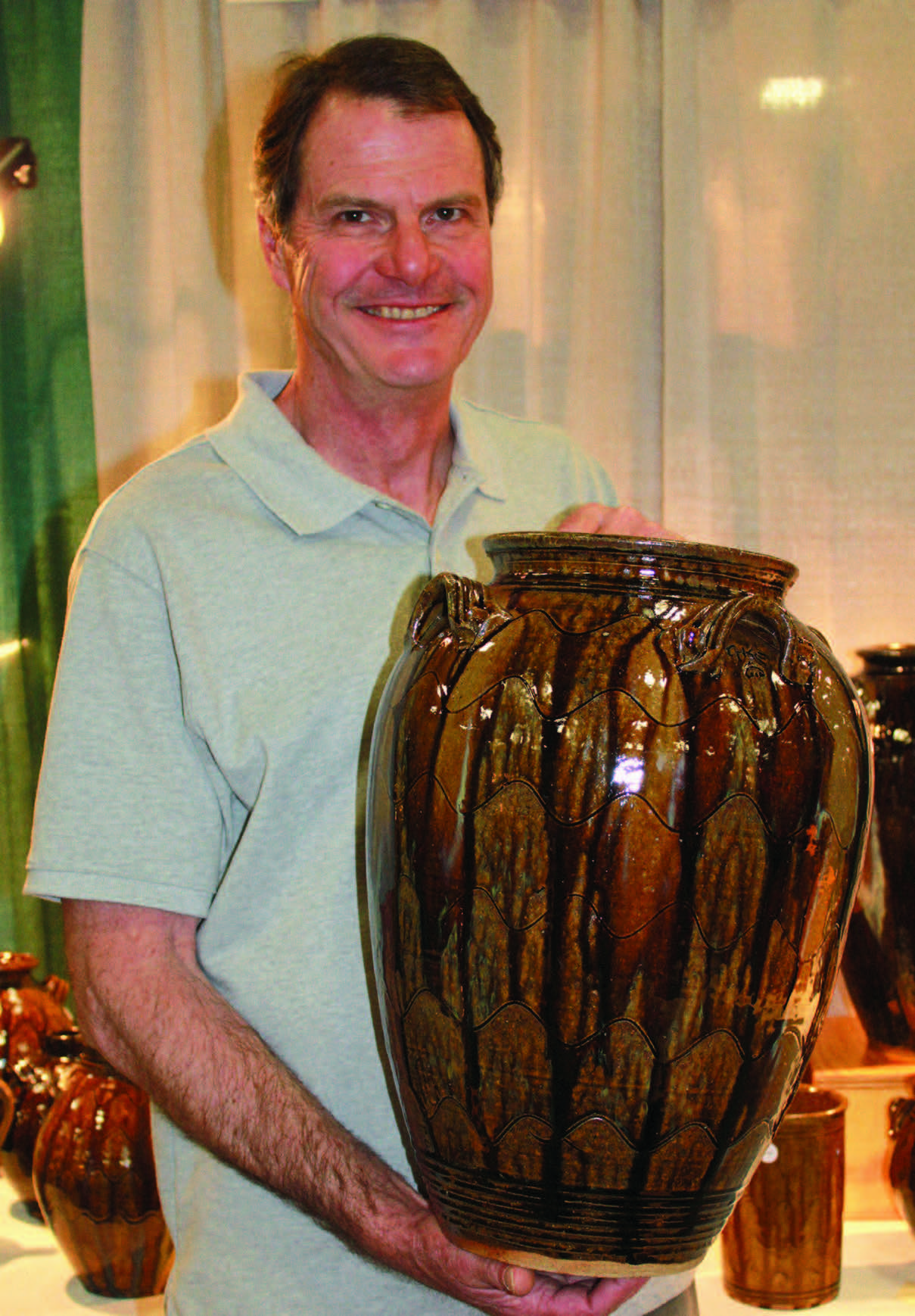 Ellington holding a five-gallon jar he made. The alkaline glaze traditionally used by Catawba Valley potters like Ellington derives its vivid, varied color from the area's mineral-laden soils. Catawba Valley Pottery and Antiques Festival, Hickory, North Carolina, 2012. Photograph by Karen Duffy.