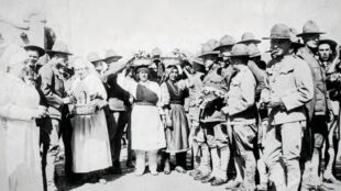 "The Red Cross and Native American women giving ""the boys"" fruit, cigarettes, and handkerchiefs, ca. 1918. Courtesy of the Center for Southwest Research, UNM, Number 000-885(8)-0012."
