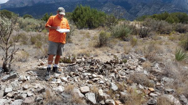 Sandia/Tijeras SiteWatch volunteer Lee Riley documents a site in the Sandia Mountains. Photograph courtesy Sandra Arazi-Coambs.