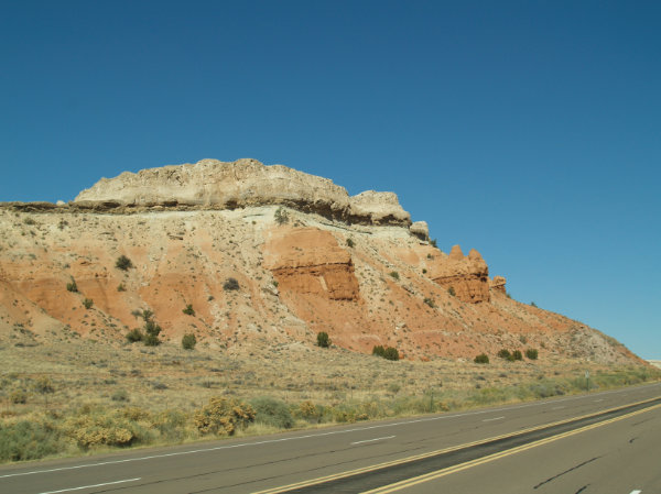 Figure 3: Colorado Plateau: Cliff along Highway 550 near San Ysidro, New Mexico. The colorful rock layers are flat-layered Mesozoic Era rocks from the age of dinosaurs. From bottom to top are Triassic Period rocks in the valley, with Jurassic Period sandstone, limestone, and gypsum above. They are topped in some places with Cretaceous Period rocks. Photograph by Jayne C. Aubele, New Mexico Museum of Natural History and Science.