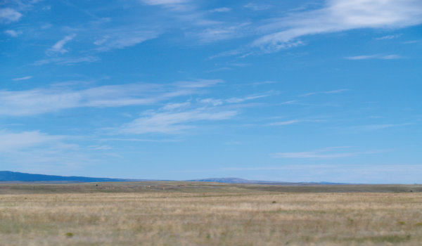 Figure 6: Great plains near Las Vegas, New Mexico: Beneath the extensive grasslands are flat-lying old terrestrial and marine rocks that contain resources such as water, and in some places, oil and gas. In the distance are the southernmost Rocky Mountains. Photograph by Jayne C. Aubele, New Mexico Museum of Natural History and Science.