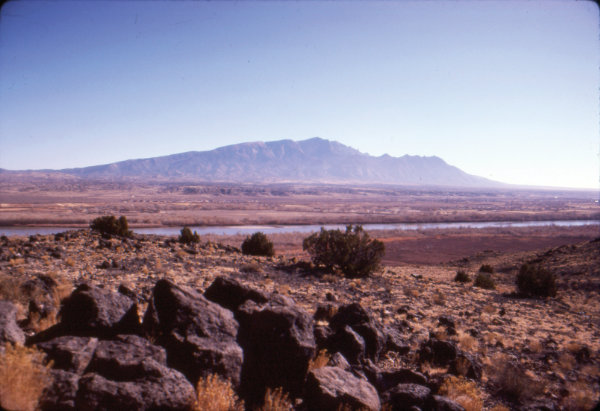 Figure 8: Rio Grande rift: Sandia Mountains and Rio Grande viewed from Bernalillo, New Mexico. The Sandia mountains are called fault-block mountains. The entire range has been lifted up along the eastern marginal faults of the Rio Grande rift, as the rift formed, and the rocks have tilted toward the east like an open trap door. The river took advantage of the low regions of the rift as it developed into a major waterway between one and four million years ago. Photograph by Jayne C. Aubele, New Mexico Museum of Natural History and Science.
